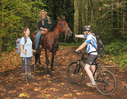 Hiker, Olivia Thomas visits with a horseback rider and mountain biker as they meet on the trail near a card draw station during the 2013 Poker Ride/Hike event.